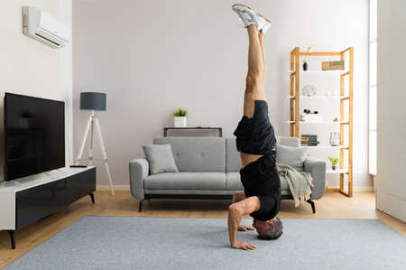 Mature Man Doing Yoga Headstand Exercise Training At Home