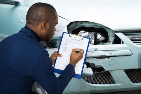 African American Car Insurance Agent Inspecting Accident Claim