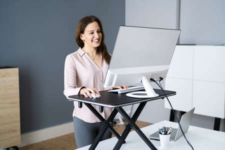 Adjustable Height Desk Stand In Office Using Computer Standard-Bild