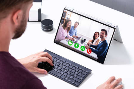 Businessman Video Conferencing With His Colleagues On Hybrid Laptop On Desk In Office