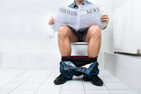Close-up Of A Man Sitting On Commode Reading Newspaper Standard-Bild