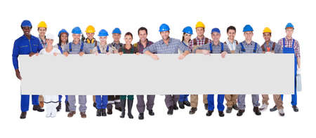 Group Of Construction Workers Holding Placard Over White Background
