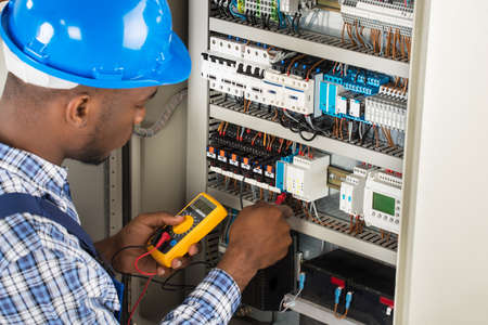 Close-up Of Male Electrician Checking Fuse Box With Multimeter Banco de Imagens