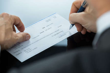 Close-up Of Businessman Hand Filling Blank Cheque At Desk