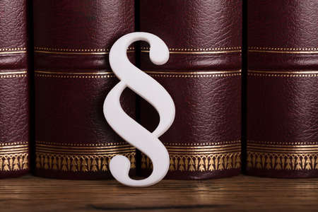 Close-up Of White Paragraph Symbol Leaning On Law Books In Courtroom