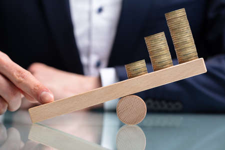 Close-up Of A Businessperson Balancing Increasing Stacked Coins With Finger On Seesaw