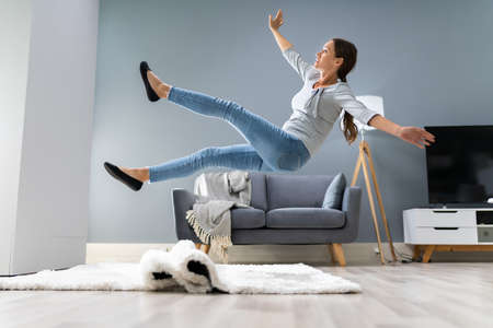 Photo Of Woman Stumbling With A Carpet In The Living Room At Home