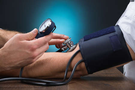 Cropped image of male doctor checking blood pressure of patient at table