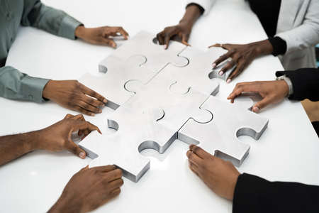 Overhead Teamwork Meeting Solving Jigsaw Puzzle. African Businesspeople