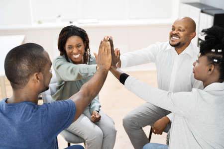 Motivational Business Meeting At Workplace. African Hands Giving High Five