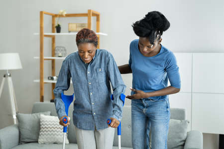 Helping Injured Handicapped African Woman With Crutches