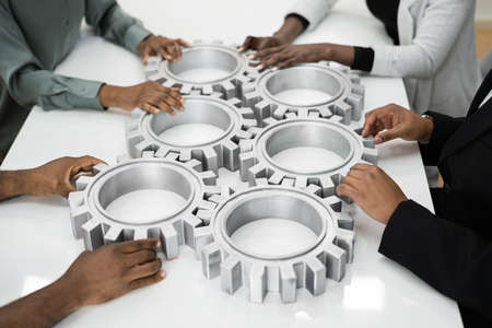 Business People Team Hands Connecting Gears. Implementation And Collaboration