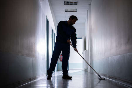Professional Office Janitor Worker Cleaning Floor With Mop