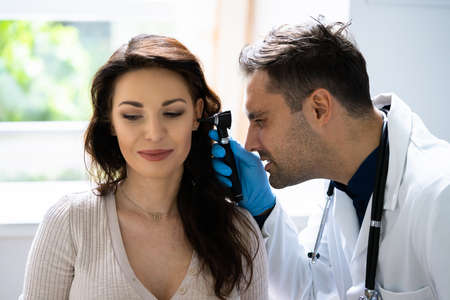 Close-up Of A Doctor Examining Patient's Ear With Otoscope Imagens