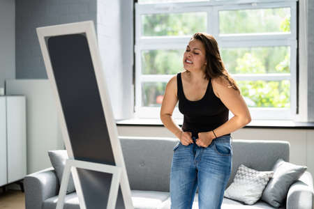 Woman Struggling With Tight Jeans. Weight Gain