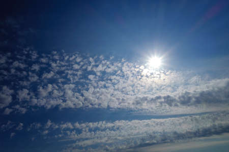 The suns rays shine in fantastic clouds. Sunny day concept, with copy space