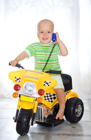 Cute boy sitting on motorcycle. At window background Stock Photo - 2215104