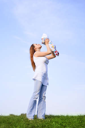 Mother with little  at nature. Blue sky. Green grass Stock Photo - 3758931