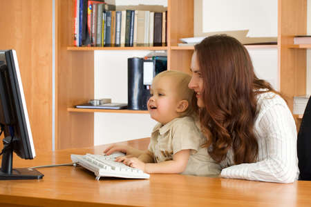 Mother with kid looking computer monitor in office  photo