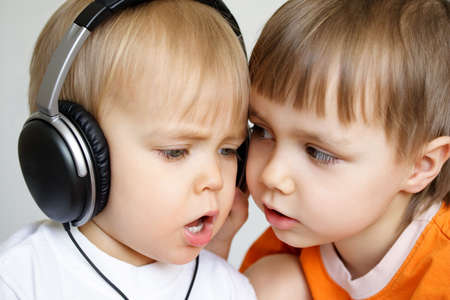 Two singing boys. One with black headphones photo
