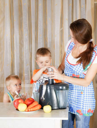 Mother with two kids doing juice from juicing machine at kitchen photo