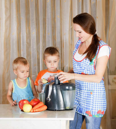 Mother with two kids doing juice from juicing machine at kitchen Stock Photo - 5771936