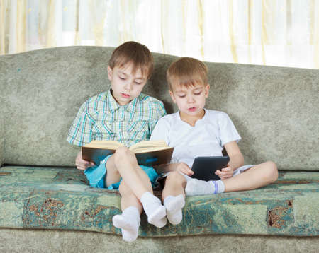 Two reading boys at sofa  One with paper book, other with electronic book photo