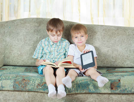 Two reading boys at sofa  One with paper book, other with electronic book Stock Photo - 12843972
