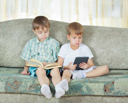 kindle: Two reading boys at sofa  One with paper book, other with electronic book Stock Photo
