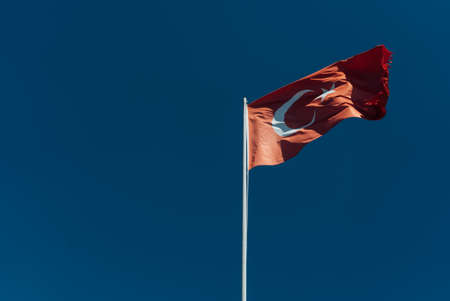 Turkish flag on long metal iron pole waving in blue sky. Red flag featuring a white star and crescent. Flag is often called al bayrak and is referred to as al sancak in the Turkish national anthem. Banco de Imagens