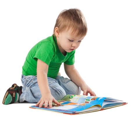 one little boy: Enthusiastic little boy with a book sitting on the floor, isolated on white Stock Photo