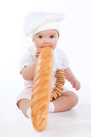 Little baker baby girl with a long loaf, isolated on white background  photo