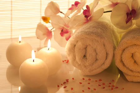 spa therapy: Spa towels, candle and orchid on bamboo background