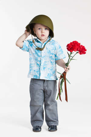 Boy with army helmet and carnations, isolated on white