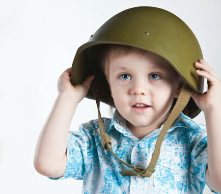 conscription: Boy with army helmet isolated on white