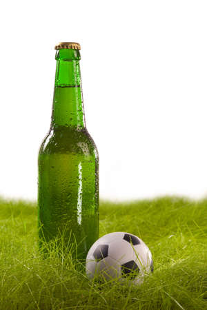 Bottle of beer with drops and small soccer ball on the grass  Isolated on white  photo