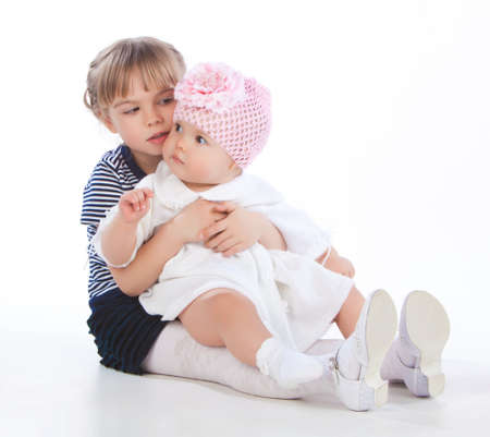 little girl communicates with her baby sister, children are isolated on white