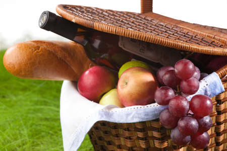 Picnic basket with wine, fruits and baguette on green grass, isolated on white background photo