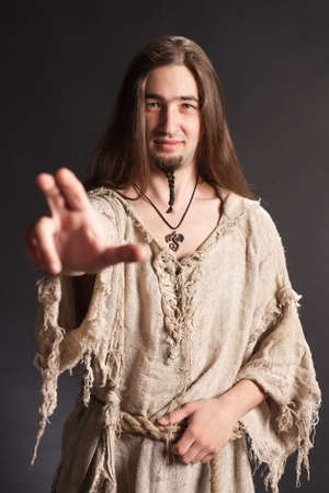 paganism: Handsome asian man with long hair makes a gesture blessing