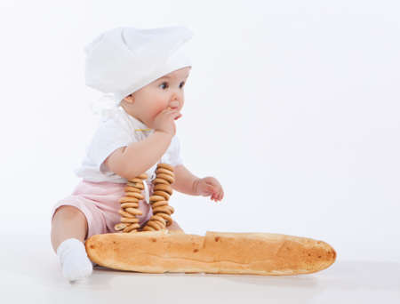 Little baker baby girl with a long loaf and bagels, isolated on white background photo