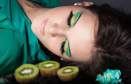 beautiful woman with green make-up laying down photo