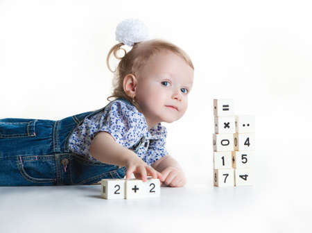 Little girl playing with blocks and looking at the camera, isolated on white background