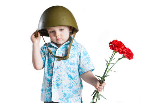 Boy with army helmet and carnations in his hand, isolated on white photo
