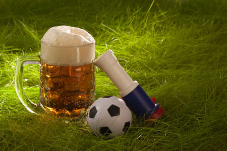 Mug of fresh lager, vuvuzela and small soccer ball on the grass.