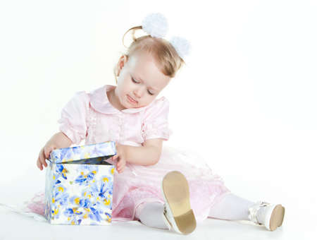 Little girl opening the present, isolated on white background photo