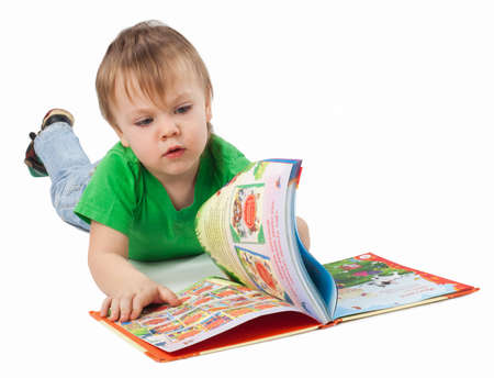 Little boy with a book laying on the floor, isolated on white