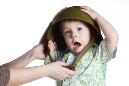 conscription: Frightened boy with army helmet isolated on white