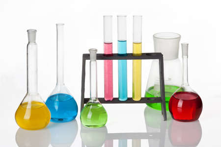 Set of laboratory glassware filled with multicolored liquids, isolated on white. photo
