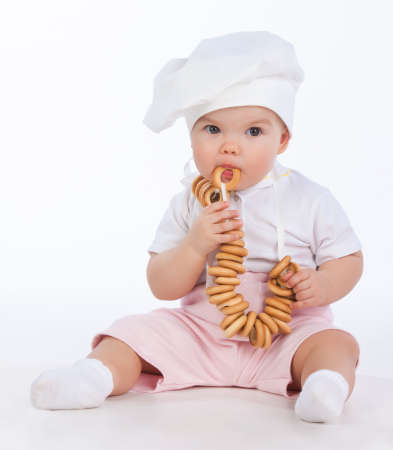bublik: Little baker baby girl with bagels, isolated on white