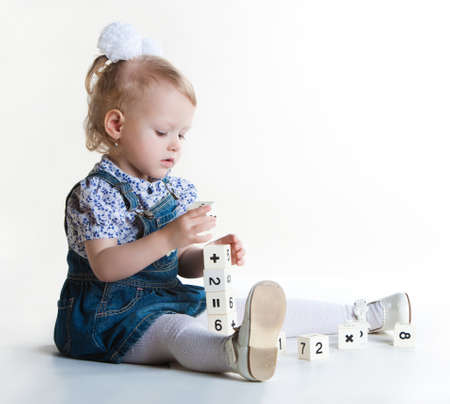 additional training: Little girl playing with blocks on white background